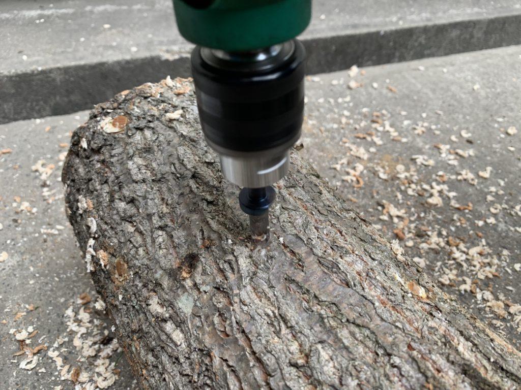 電気ドリルで原木に穴をあけていく様子