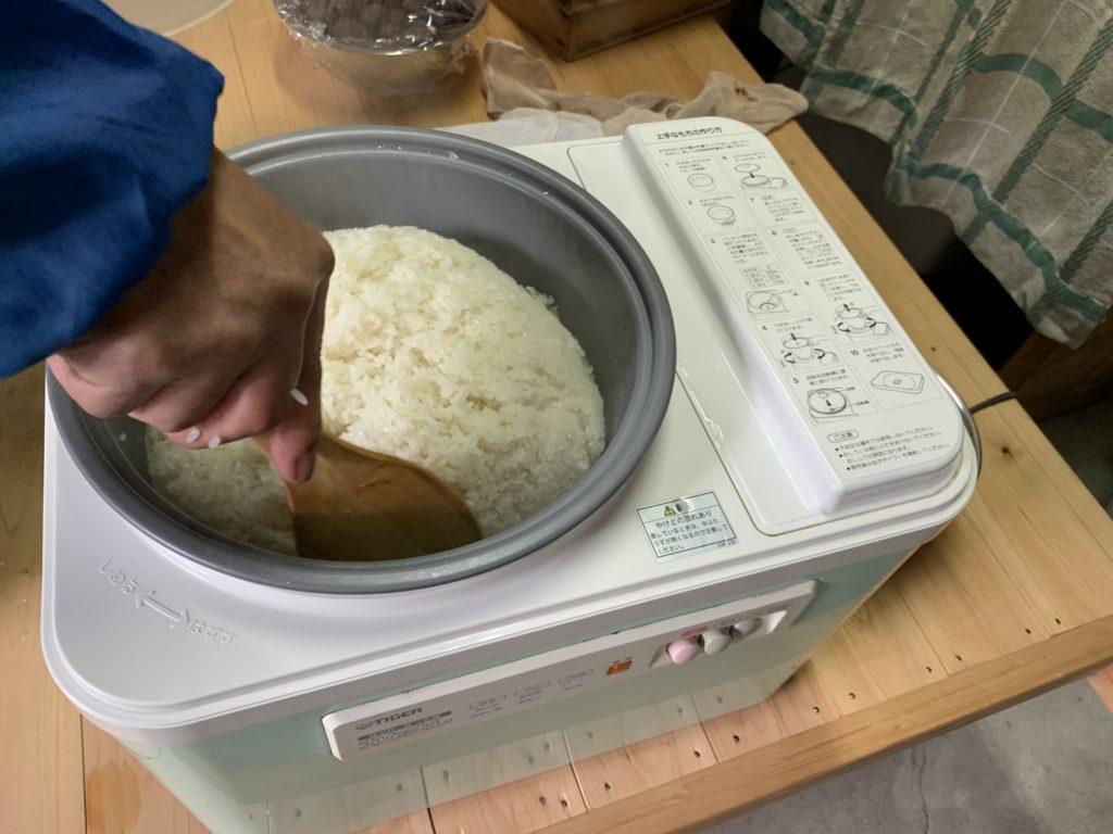 餅つき機の中のもち米を木べらで押さえる様子