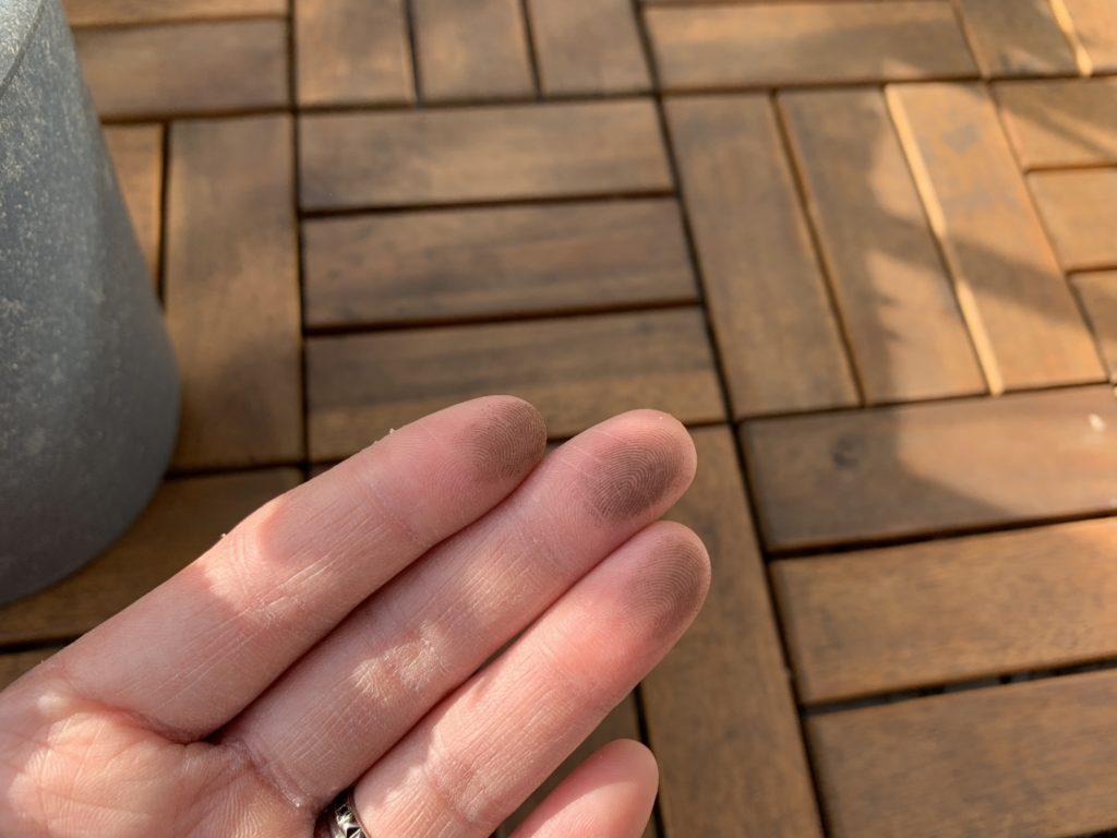 ウッドデッキパネルを指でこすると真っ黒になった様子
