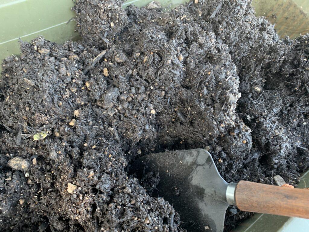 プランターの土をかき混ぜる様子